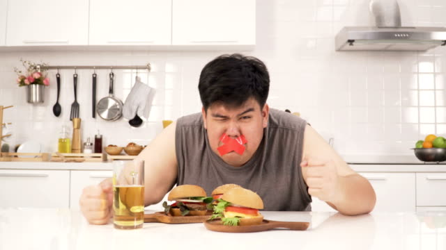 Thai overweight man is prohibited to eat unhealthy foods such as hamburger and beer