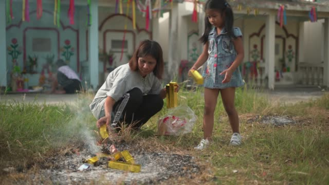 Thai people burning sacrificial offering in grave