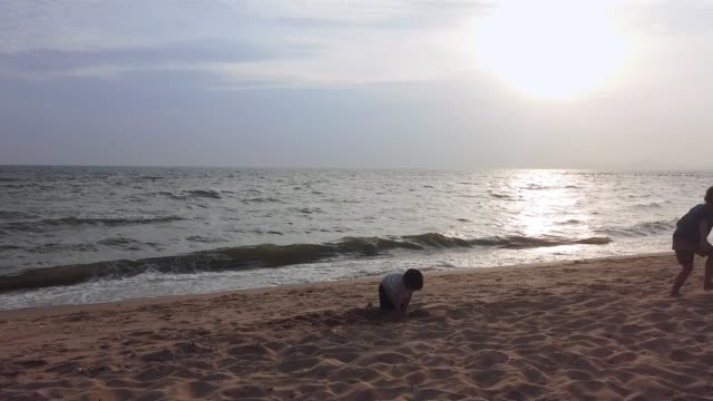 Thai Siblings is playing and running on a summer beach with shadow silhouette sunset.