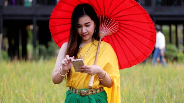 Thai woman dressing with traditional style using mobile phone video