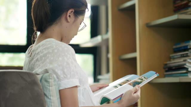 stockvideo's en b-roll-footage met thaise vrouw is het lezen van boek bij de bibliotheek naast het venster - woman home magazine