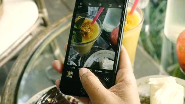 thai frau photographieren essen im restaurant - bloggen stock-videos und b-roll-filmmaterial