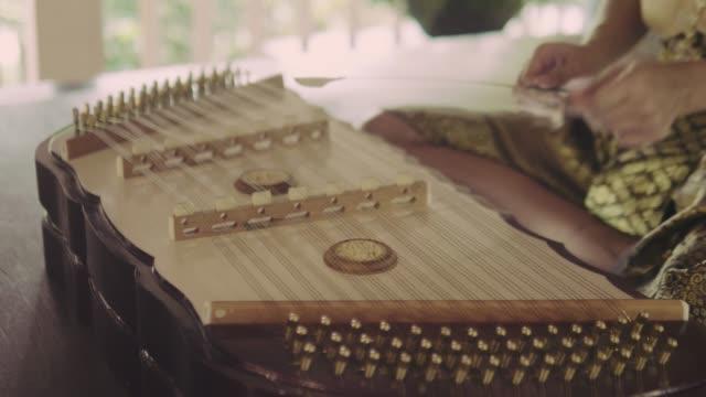 Thai woman playing Thai wooden dulcimer musical instrument