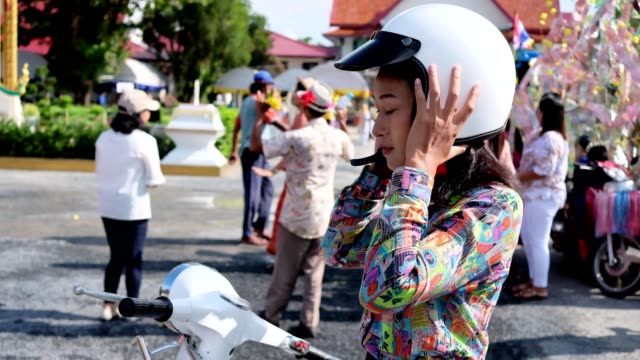 Thai women and retro scooter in tradition Thai temple