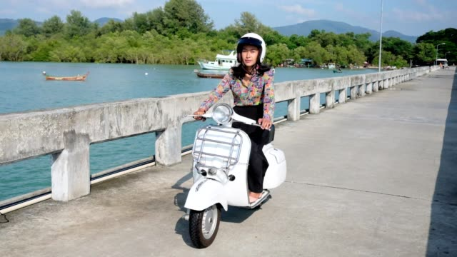 Thai women driving retro scooter
