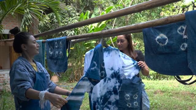 Thai women tie batik dyeing indigo color hanging process dry clothes in the sun