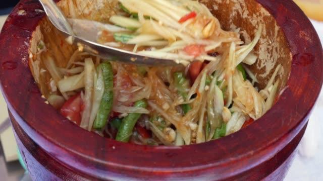vídeos de stock, filmes e b-roll de mulheres tailandesas que preparam o som verde da salada da papaia no almofariz de madeira com pilão. feche acima. 4k - comida salgada