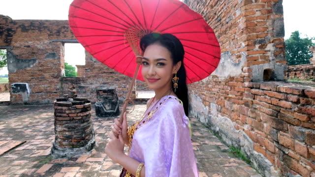 vídeos de stock, filmes e b-roll de mulher jovem tailandesa vestindo traje nacional de tailândia andando no templo antigo em ayutthaya - mundial da unesco cidade historic. bem-vindo ao conceito de tailândia. - cultura tailandesa