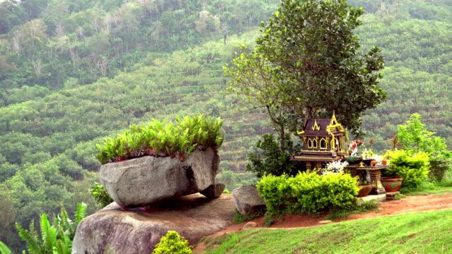 thailand spirit house ,san phra phum, rean tevoda, pteah phum, in green mountains of phuket island. rock and grass. fullhd - burma home do стоковые видео и кадры b-roll