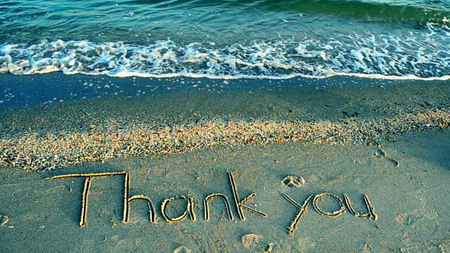 Thank you handwritten in sand on a beach video