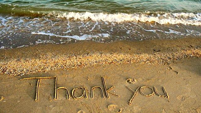 vídeos de stock, filmes e b-roll de obrigado, escrito à mão na areia em uma praia - agradecimento