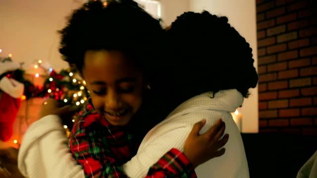 vídeos de stock, filmes e b-roll de grato afro-americana mãe de menina abraçando na manhã de natal - agradecimento