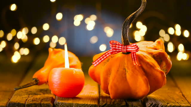 thanksgiving decoration with pumpkins and greeting card on illuminated background and a rustic wooden table - thanksgiving background stock videos & royalty-free footage