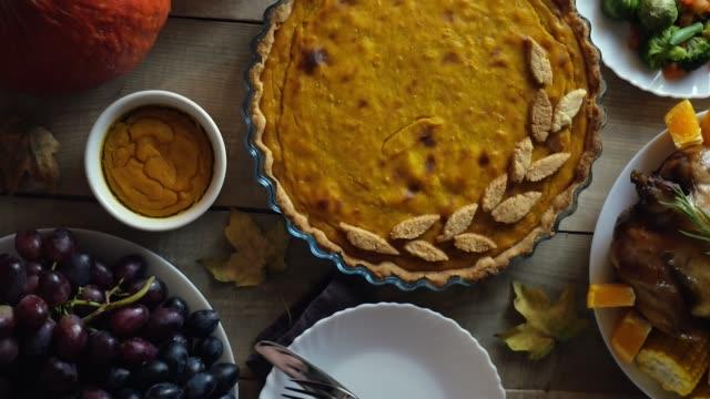 感恩節南瓜。木製背景的傳統餡餅。南瓜派。那個女人正在切餡餅。感恩節。 - pumpkin pie 個影片檔及 b 捲影像