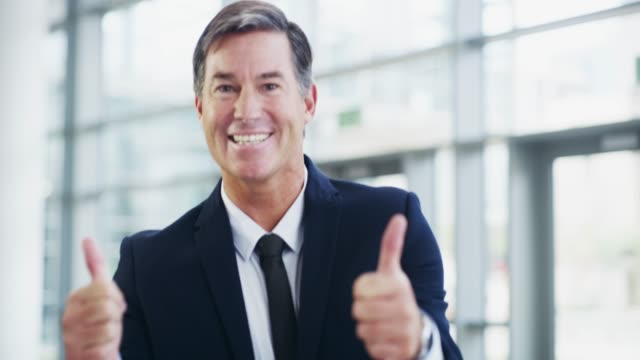 That was all kinds of awesome 4k video footage of a mature businessman showing thumbs up while walking through a modern office thank you stock videos & royalty-free footage