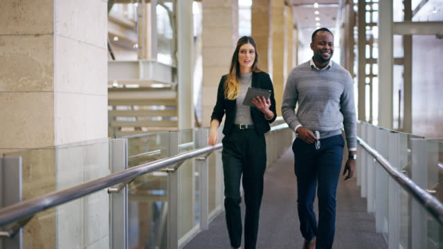 That's great! 4k video footage of two young businesspeople walking through their office building bolos stock videos & royalty-free footage