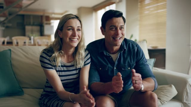 That's the spirit! 4k footage of a couple watching something together at home watching tv stock videos & royalty-free footage