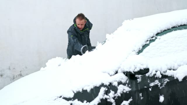 ''that's why i hate snow!''- young man cleaning the snow from a car - car chill video stock e b–roll