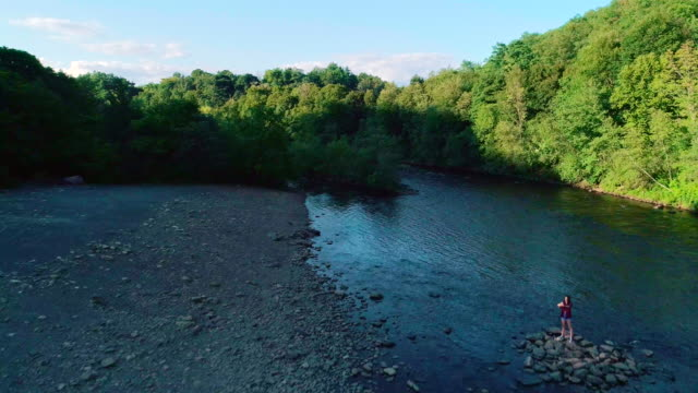 The 16 years old teenager girl make selfiein front of he scenic view of the Lehigh River near by Jim Thorpe, Pennsylvania, at sunset. Aerial drone video.