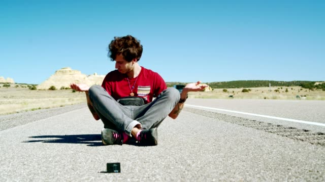 The 30-years-old hipster, vlogger, posing in front of the action camera when he is sitting on the highway in Utah, USA. video