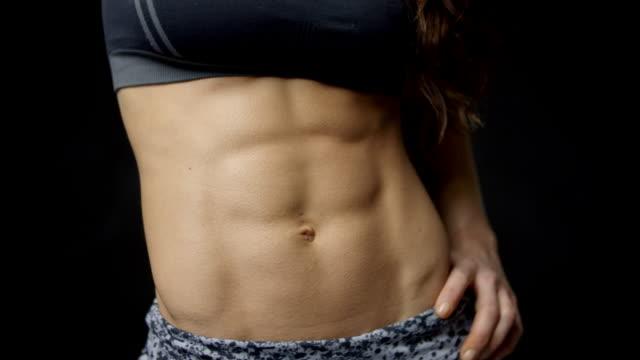 the abs of muscular woman with hand on hip, close up shot - спортивный бюстгальтер стоковые видео и кадры b-roll