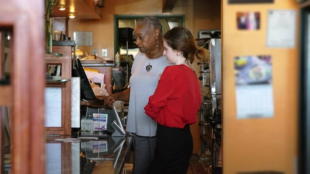 the active, positive senior 77-years-old black businesswoman teaching the young caucasian white girl how to use the cash register in the restaurant - настоящая жизнь стоковые видео и кадры b-roll