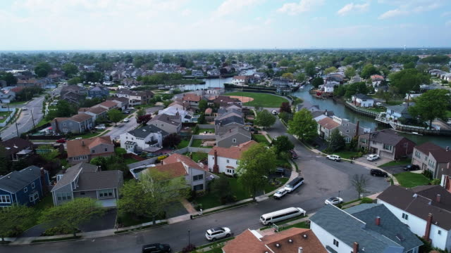The aerial drone view to a wealthy residential district in Oceanside, Queens, New York City, with houses with pools on backyards and piers with boats along the channels. Panning camera motion.