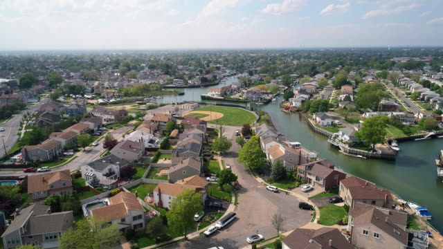 The aerial drone view to a wealthy residential district in Oceanside, Queens, New York City, with houses with pools on backyards and piers with boats along the channels. Descending camera motion.