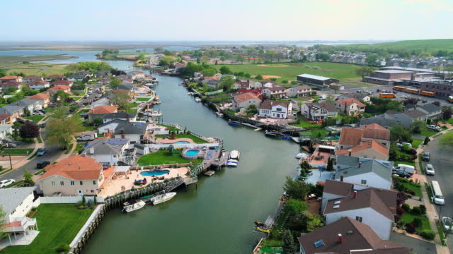 The aerial drone view to a wealthy residential district in Oceanside, Queens, New York City, with houses with pools on backyards and piers with boats along the channels. Forward camera motion.