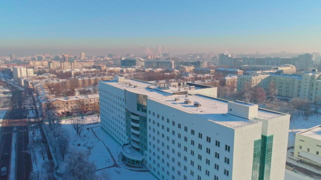 The aerial panoramic view on the winter city covered by the snow in the bright cold sunny day. Orbit camera motion. The aerial panoramic view on the residential district of the winter city covered by the snow in the bright cold sunny day. 4K UHD video footage with orbit camera motion. Minsk, Belarus, Eastern Europe medical building stock videos & royalty-free footage