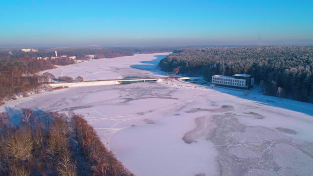 the aerial scenic panoramic view on the frozen river and forest at sunset. - беларусь стоковые видео и кадры b-roll
