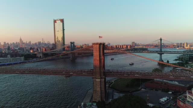The aerial scenic view to Manhattan Downtown and Brooklyn Bridge from Brooklyn Heights over the East River at the sunset. Wide orbit motion.