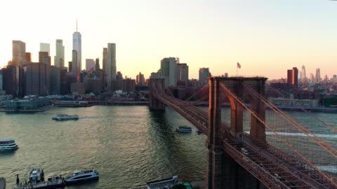 vidéos et rushes de la vue aérienne panoramique à manhattan downtown et brooklyn bridge de brooklyn heights, sur l'east river au coucher du soleil. - horizon urbain