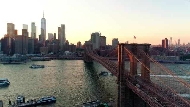 die malerische luftbild downtown manhattan und brooklyn bridge aus brooklyn heights über den east river in den sonnenuntergang. - turm bauwerk stock-videos und b-roll-filmmaterial