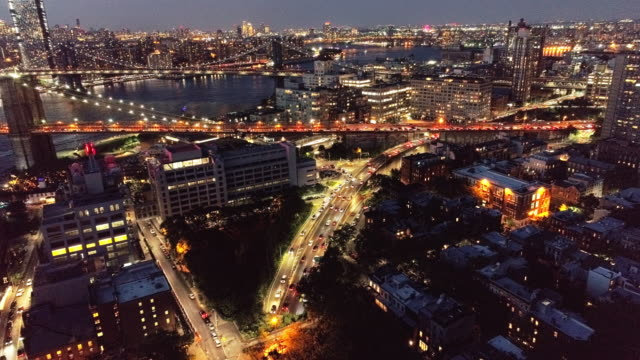 The aerial static view of the traffic at the entrance to Brooklyn Bridge from Brooklyn, NY The aerial panoramic night view of the traffic at the entrance to Brooklyn Bridge from Brooklyn, NY. 4K UHD drone video footage with the static camera. manhattan bridge stock videos & royalty-free footage