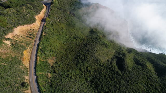 vídeos de stock e filmes b-roll de the aerial video of the low clouds forming over the pacific ocean. the view from a drone above clouds, in the mountains nearby big sur, cabrillo highway, californian west coast, usa. static camera. - estrada 001