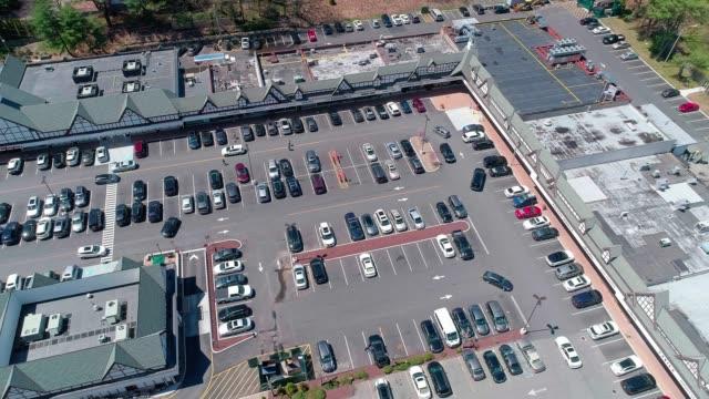 vídeos de stock, filmes e b-roll de o vídeo aéreo do tráfego no estacionamento do centro comercial, na pequena cidade de americana - shopping center