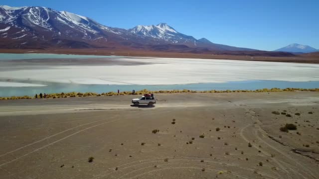 vídeos de stock e filmes b-roll de the aerial view of an off road car driving along the coast of turquoise tranquil lake with the background of mountain range and clear blue sky in sunny day. - américa do sul