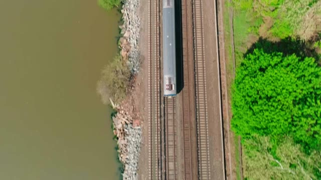 the aerial view of the passenger train passing along the hudson river near by dobbs ferry, westchester county, new york, usa - tor kolejowy filmów i materiałów b-roll