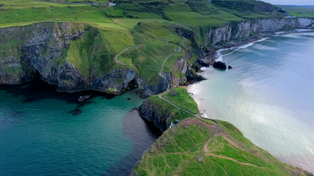 the aerial view of the two islands in carrick-a-rede in ireland - paesaggio marino video stock e b–roll