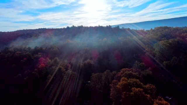 The aerial view on the fog over the mountain's forest in Appalachian, Poconos, Pennsylvania, at early morning during the fall foliage season. Shooting against the sun, with lens flare and sunbeamsAerial drone video. video