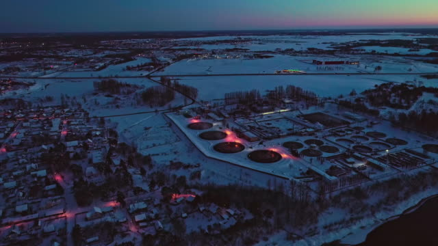 the aerial view on the waste wastewater treatment facilities and power plant in the industrial zone at sunset in winter. - беларусь стоковые видео и кадры b-roll