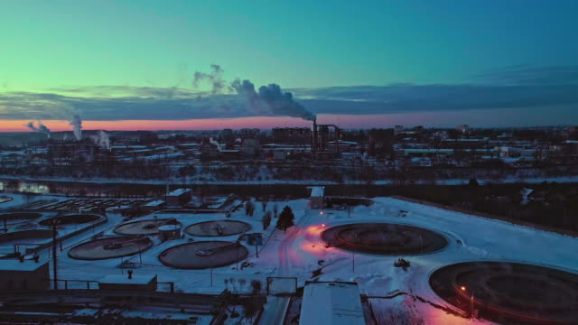 the aerial view on the waste wastewater treatment facilities and power plant in the industrial zone at sunset in winter. - białoruś filmów i materiałów b-roll