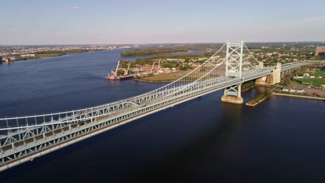 The aerial view over the Benjamin Franklin Bridge across the Delaware River from Philadelphia, PA to Cadmen, NJ The aerial view from the waterfront over the Benjamin Franklin Bridge across the Delaware River from Philadelphia, Pennsylvania to Cadmen, New Jersey. USA, North America. The sunny day. 4K UHD drone video suspension bridge stock videos & royalty-free footage