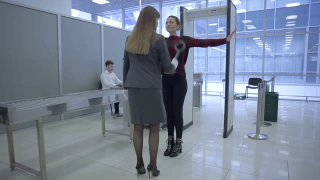 The airport worker scans a woman's body with hand scanner in the airport video