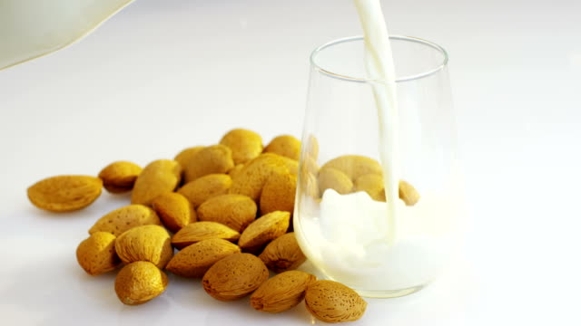 vídeos de stock e filmes b-roll de the almond milk is poured into a glass in slow motion, the background in woods there are almonds, perfect for a diet for a healthy diet and can be used as medicine. - amendoas