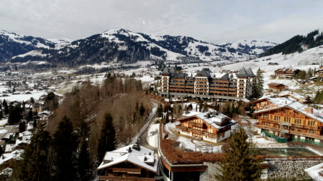The Alpina Gstaad hotel in winter snowfall - Aerial 4K Gstaad, Bern - Switzerland Drone DJI Phantom 4 PRO 4K - 25fps - 13 sec. chalet stock videos & royalty-free footage