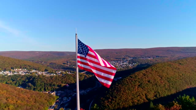 the american flag flying on the high flagpole over the appalachian mountains, poconos, pennsylvania, near by jim thorpe - горы поконо стоковые видео и кадры b-roll