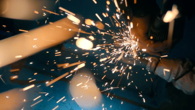 vídeos de stock e filmes b-roll de the angular grinding machine is cutting the pipe and flying a lot of sparks - moedor