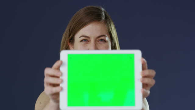 The app that's working for me 4k video footage of a young businesswoman holding a digital tablet with a green screen against a gray studio background representing stock videos & royalty-free footage